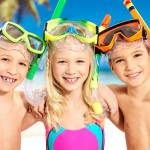 Portrait of the happy children enjoying at beach.  Schoolchild k